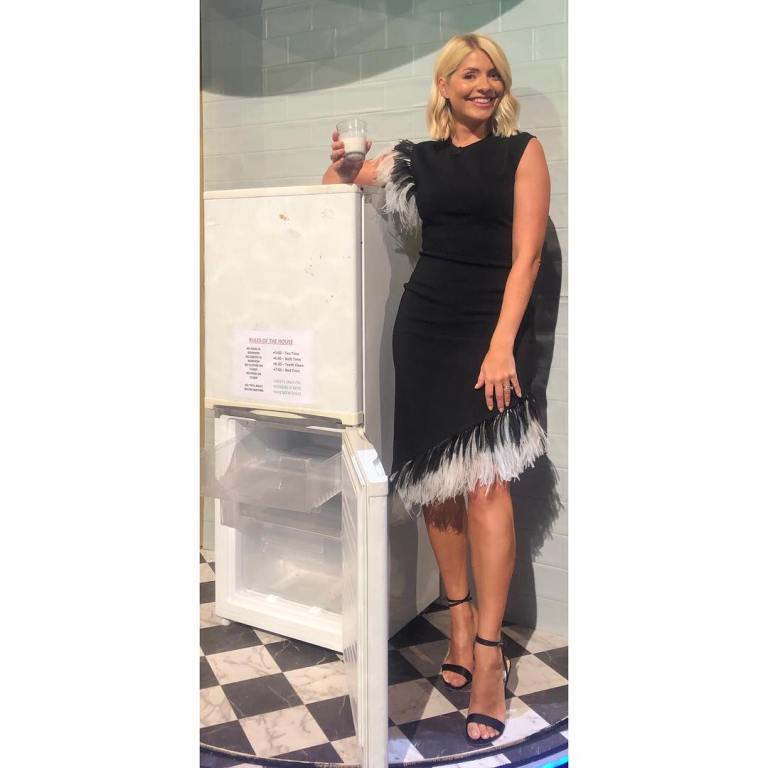 where to get Holly willoughby black sleeveless dress with black and white feather dress standing nex to a fridge May 2019 photo Holly Willoughby