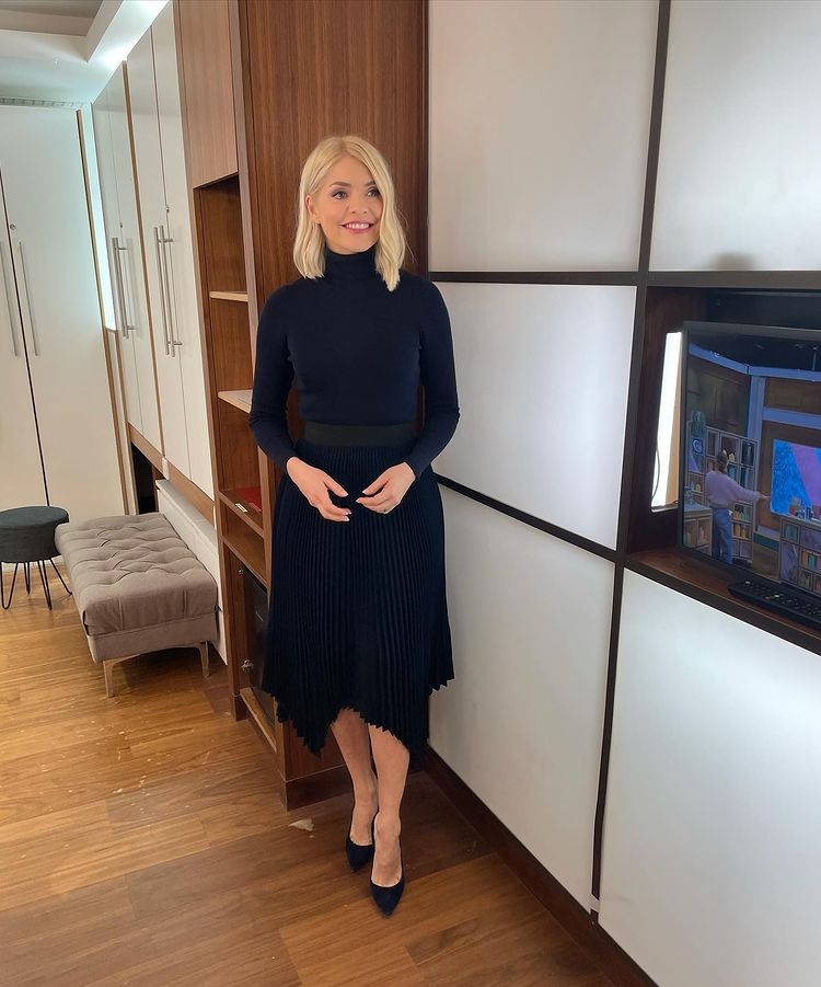 where to get all Holly Willoughby This Morning outfits navy pleated skirt navy polo neck navy suede court shoes 10 March 2021 Photo Holly Willoughby