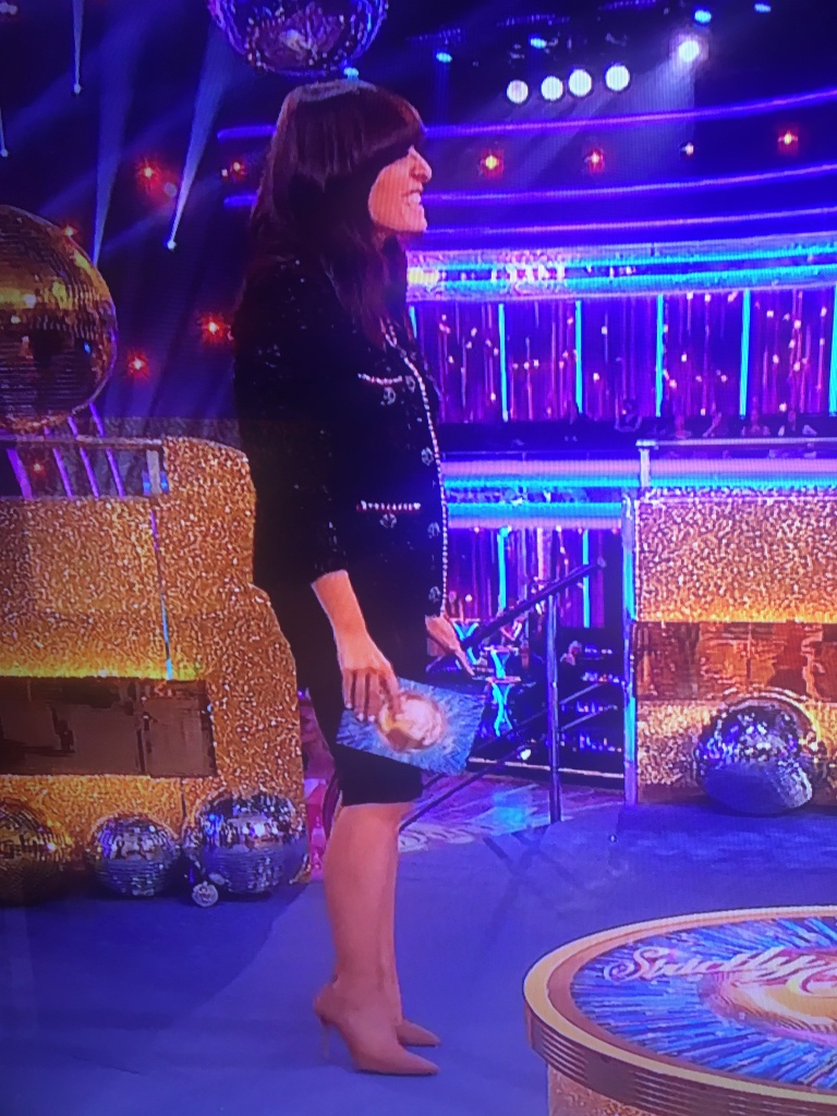 where to get all Claudia Winkleman Strictly Come Dancing outfits metallic embellished black cardigan black skirt nude suede court shoes 10 October 2021 Photo BBC v2